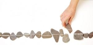 Alte Hand schiebt einen Stein in eine passende Linie